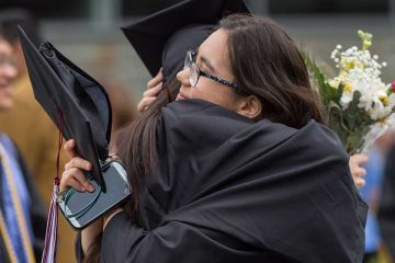 Graduates hug after commencement 2018