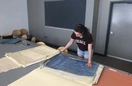 Student stands at table and leans over blueprints