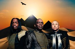 Earth, Wind, & Fire promotional poster featuring three band members standing in front of pyramids backlit by sunshine