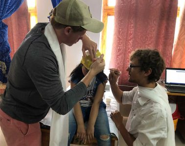 Patrick Needham '20 and a physician work with a pediatric neurology patient applying a cap that will allow them to run tests