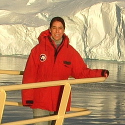 Portrait of Prof. Amy Leventer, standing on prow of boat in front of glacier