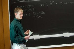 Professor Rick Geyer stands in front of chalkboard (Photo by Gerard Gaskin)