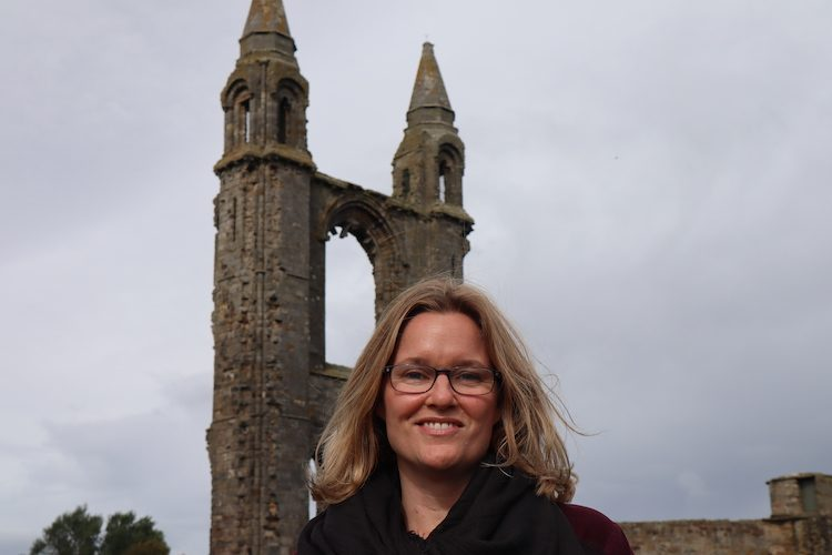 Smiling woman stands in front of religious structure on cloudy day