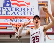 "Colgate player poses next to rim with ""Patriot League Champions"" sign"