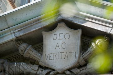 """An image of a stone carving with the motto, """"Deo Ac Veritati"""""""