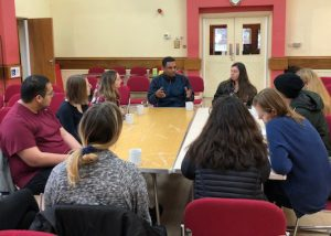 Members of the Manchester Study Group sit at table during meeting with local refugee organizations