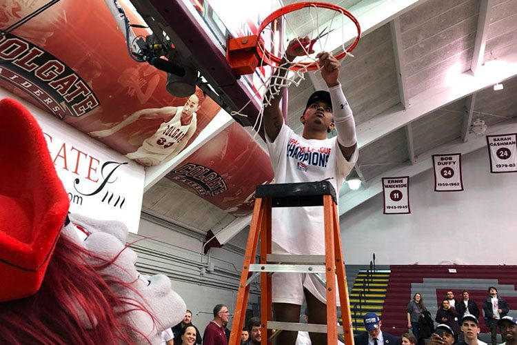 Jordan Burns '22 cuts down the net as he celebrates Colgate's first Patriot League Men's Basketball title in 23 years.