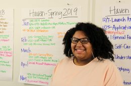 Tracia Banuelos poses in front of several posters in her office in Haven in Curtis Hall.