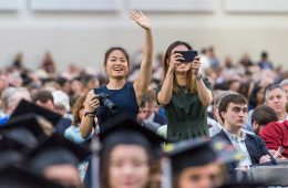 Family members with cameras wave to graduating seniors at commencement